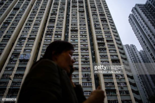 TOPSHOT A woman walks past a residential block in Hong Kong on April 27 2017 / AFP PHOTO / Anthony WALLACE