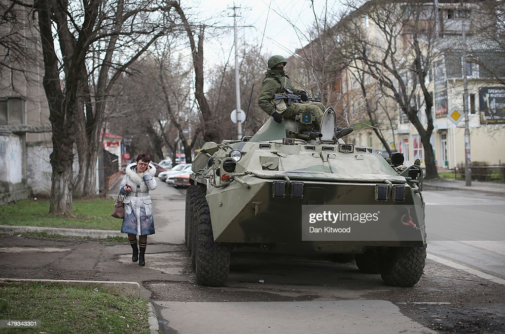 A woman walks past a Russian military personnel carrier outside a Ukrainian military base on March 18, 2014 in Simferopol, Ukraine. Voters on the autonomous Ukrainian peninsular of Crimea voted overwhelmingly yesterday to secede from their country and join Russia.