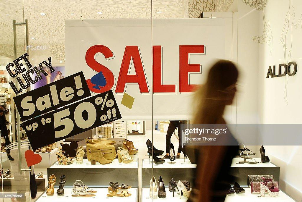 A woman walks past a sale display at Pitt Street shopping mall on December 23 2011 in Sydney Australia As retailers like Kathmandu JBHI Fi and...