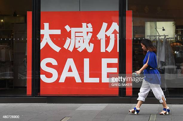 A woman walks past a sale sign at a fashion outlet in a shopping mall in Beijing on July 15 2015 China's economy expanded 70 percent yearonyear in...