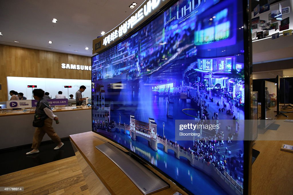 A woman walks past a Samsung Electronics Co. curved Ultra High Definition (UHD) television at the company's d'light store in Seoul, South Korea, on Monday, July 7, 2014. Samsung Electronics is scheduled to report operating profit and sales figures on July 8. Photographer: SeongJoon Cho/Bloomberg via Getty Images