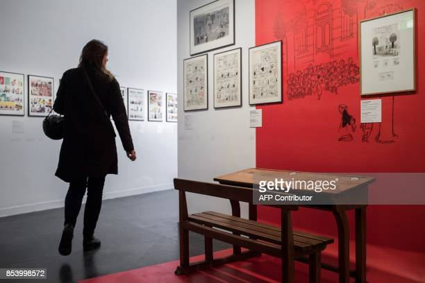 A woman walks past a school bench displayed for an installation related to the cartoon character 'le Petit Nicolas' as part of an exhibition...
