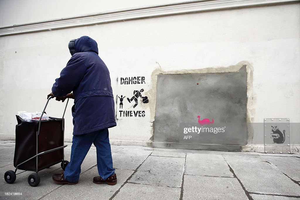 A woman walks past a section of a wall where celebrated street artist Banksy's 'Slave Labour' graffiti artwork was removed in north London on February 23, 2013. The work that showed a young boy using a sewing machine to make the British flag has been carefully removed and will be auctioned in Miami where it's expected to fetch around 328,000 GBP (500,000 USD). Residents of the North London area have reacted angrily to the removal of the work, but the auction house says the piece was acquired legally.