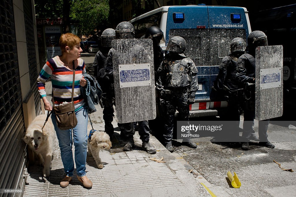 A woman walks past a security cordon of riot police officers stained by water and flour thrown by protesters in the streets of Barcelona (Spain) on May 29, 2016. Tense Sunday in the streets of the popular Gracia district of Barcelona. After the eviction of an occupied bank branch known as the Banc Expropiat (Expropiated Bank) on past Monday 23 riots have been happening following days. Today hundreds of protesters tried to enter the building again guarded by riot police officers.