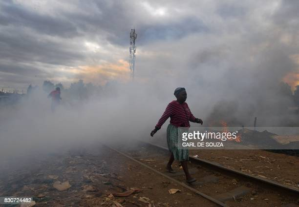 TOPSHOT A woman walks past a shack which was burnt to the ground by protestors in the Kibera slum in Nairobi on August 12 2017 Three people including...