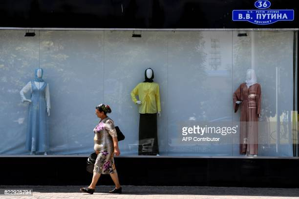 A woman walks past a shop selling Islamic clothes for women on an avenue named after Russian President Vladimir Putin in central Grozny on July 26...