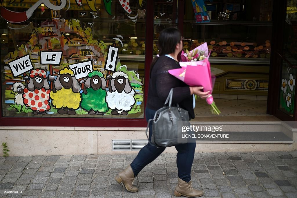 A woman walks past a shop window bearing drawings of sheeps, painted with colors of Tour de France's jerseys, holding placards reading 'Long life the Tour de France !' in Saint-Lo, Normandy, on June 29, 2016, three days before the start of the 103rd edition of the Tour de France cycling race. The 2016 Tour de France will start on July 2 in the streets of Le Mont-Saint-Michel and ends on July 24, 2016 down the Champs-Elysees in Paris. / AFP / LIONEL
