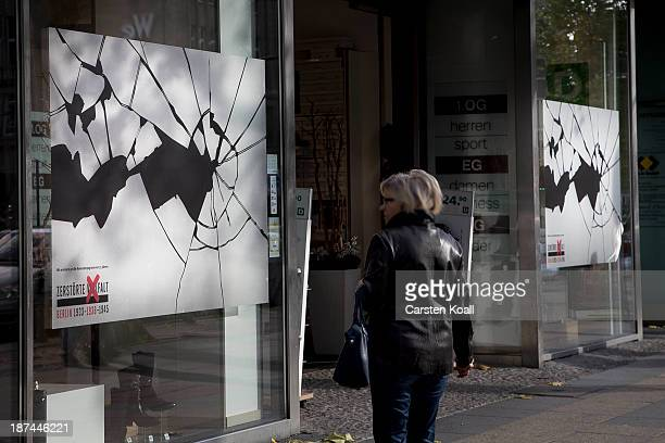 A woman walks past a shop window made to look like it has been smashed to commemorate the 75th anniversary of the Kristallnacht pogroms on November 9...