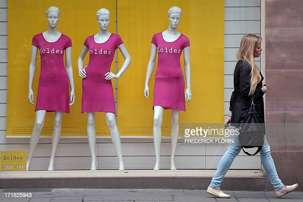A woman walks past a shop window on June 26 2013 in the eastern Frenceh city of STrasbourg on the first day of the summer sales AFP PHOTO/FREDERICK...
