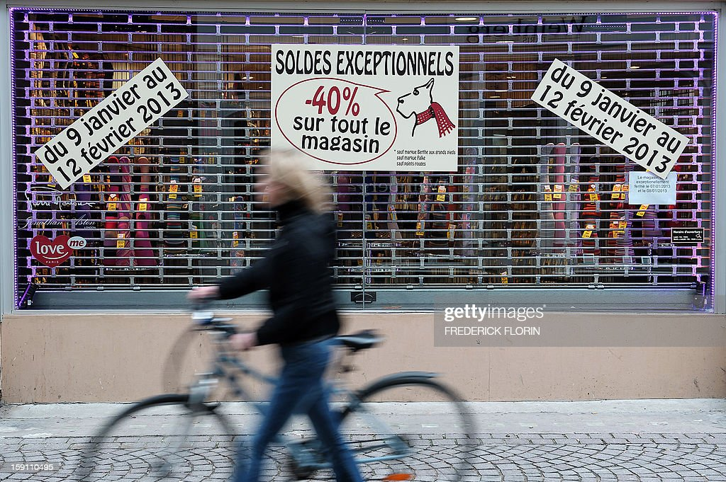 A woman walks past a shop window reading 'Exceptional Sales' on January 8, 2013 on the eve of the winter sales in Strasbourg, eastern France.