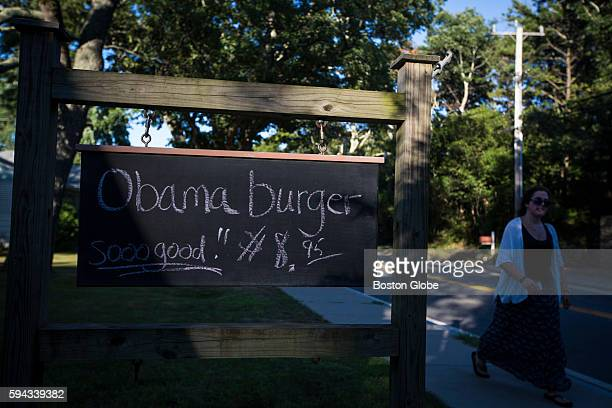 A woman walks past a sign advertising an Obama Burger at John's Fish Market in Vineyard Haven Mass on the island of Martha's Vineyard Aug 18 2016...