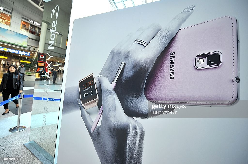 A woman walks past a sign board advertising Samsung Electronics' Galaxy Note 3 smartphone at a railway station in Seoul on October 25, 2013. South Korea's Samsung Electronics said its net profit spiked 25.6 percent to another record in the third quarter, driven by soaring revenue from memory chip sales.