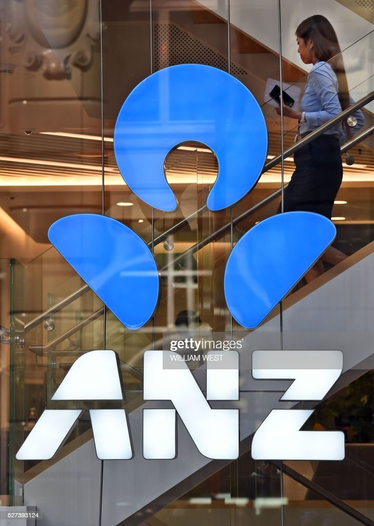 A woman walks past a sign for ANZ bank in Sydney on May 3, 2016. Bank on May 3 posted an interim net profit slump of 22 percent on the back of impairment and restructuring charges that the lender said would reposition it for the future. / AFP / William WEST