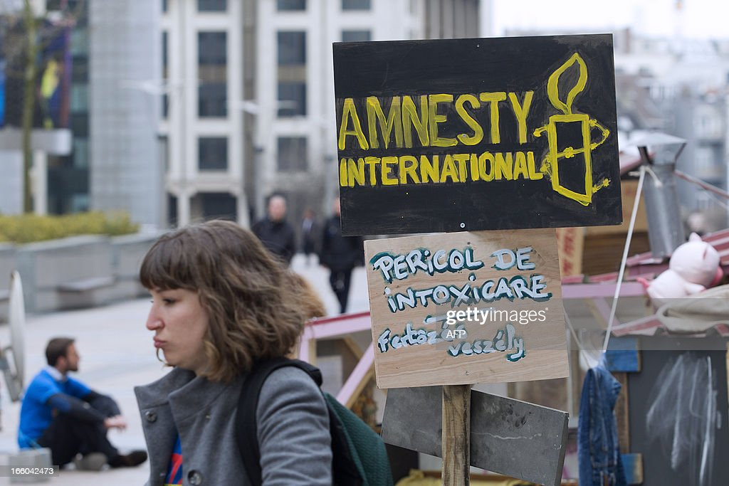 A woman walks past a sign of Amnesty Internationalduring a protest against discrimination of Roma people in Europe, on April 8, 2013 in Brussels. AFP PHOTO/BELGA/ KRISTOF VAN ACCOM -Belgium Out-