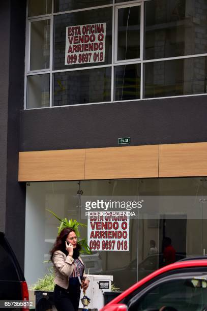 A woman walks past a sign offering an office for sale or rent in Quito on March 24 2017 The collapse of the real estate market in Ecuador is not the...