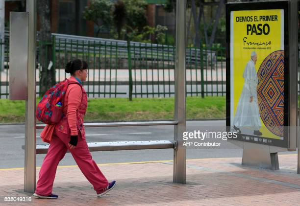 A woman walks past a sign reading 'Let's all take the first step' ahead of Pope Francis' upcoming visit in Bogota on August 23 2017 Pope Francis will...