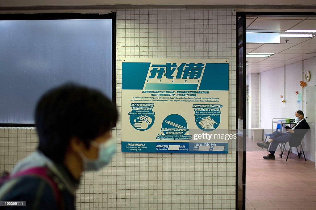 A woman walks past a sign showing an infection control notice alert level at the Princess Margaret Hospital on April 12, 2013 in Hong Kong. Local authorities have stepped up the testing of live poultry imports from China to include a rapid test for the H7N9 'bird flu' virus. Measures were put in place as the tenth victim of the influenza strain was confirmed in mainland China yesterday.