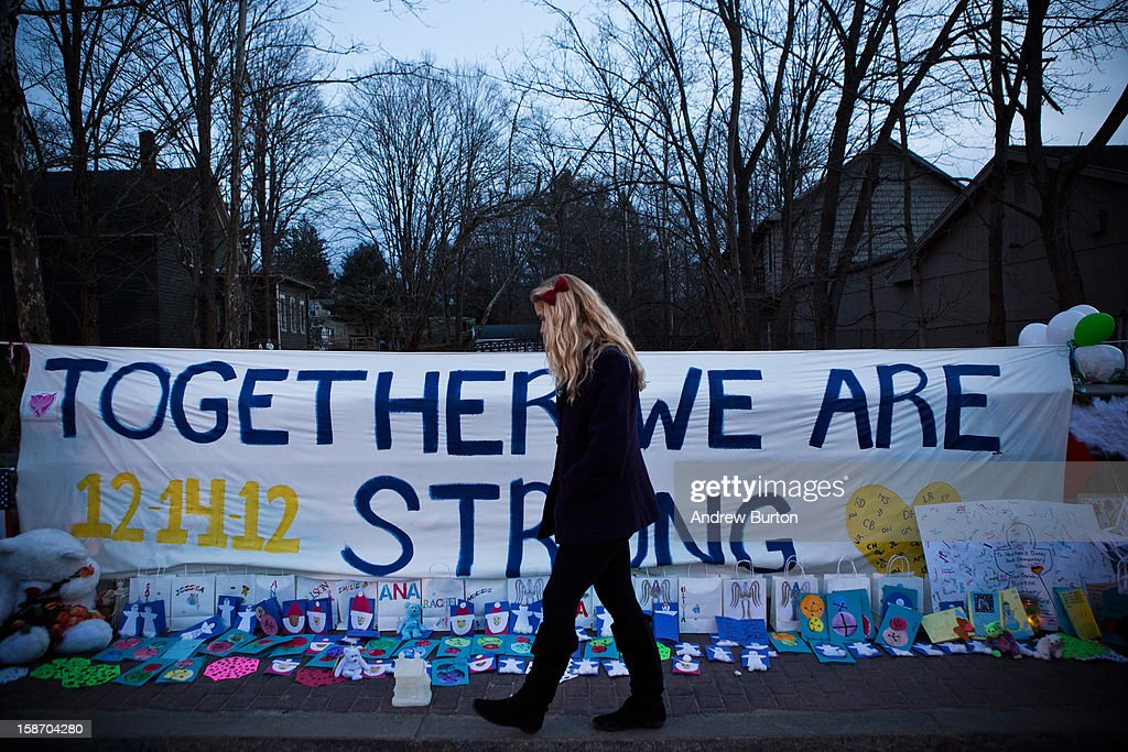 A woman walks past a sign that reads 'Together we are Strong' at a memorial for those killed in the school shooting at Sandy Hook Elementary School...
