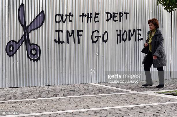 A woman walks past a slogan in central Athens on January 21 2015 Whoever wins Greece's general election on January 25 Europe will have to take urgent...