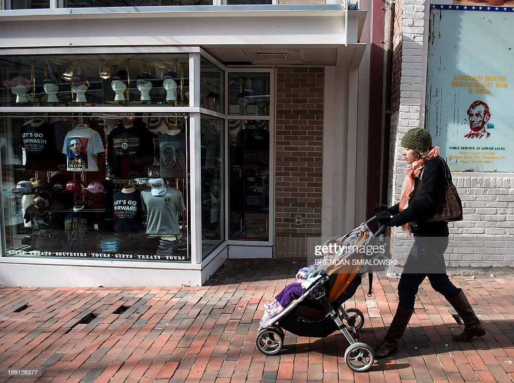 A woman walks past a souvenir shop selling Obama memorabilia in Washington on January 8, 2013. Preparations continue for US President Barack Obama's inauguration for his second term on January 21. AFP PHOTO/Brendan SMIALOWSKI