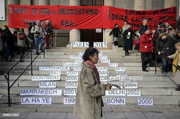 A woman walks past a stairs bearing the names of previous host cities of climate summits on November 28 2015 in Geneva during a rally ahead of the UN...