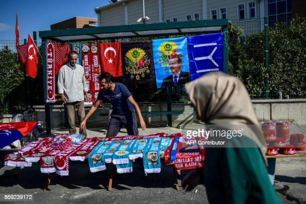 TOPSHOT A woman walks past a stall as the sellers line up scarfs of Turkish President Racep Tayyip Erdogan as they wait for customers by the Silivri...
