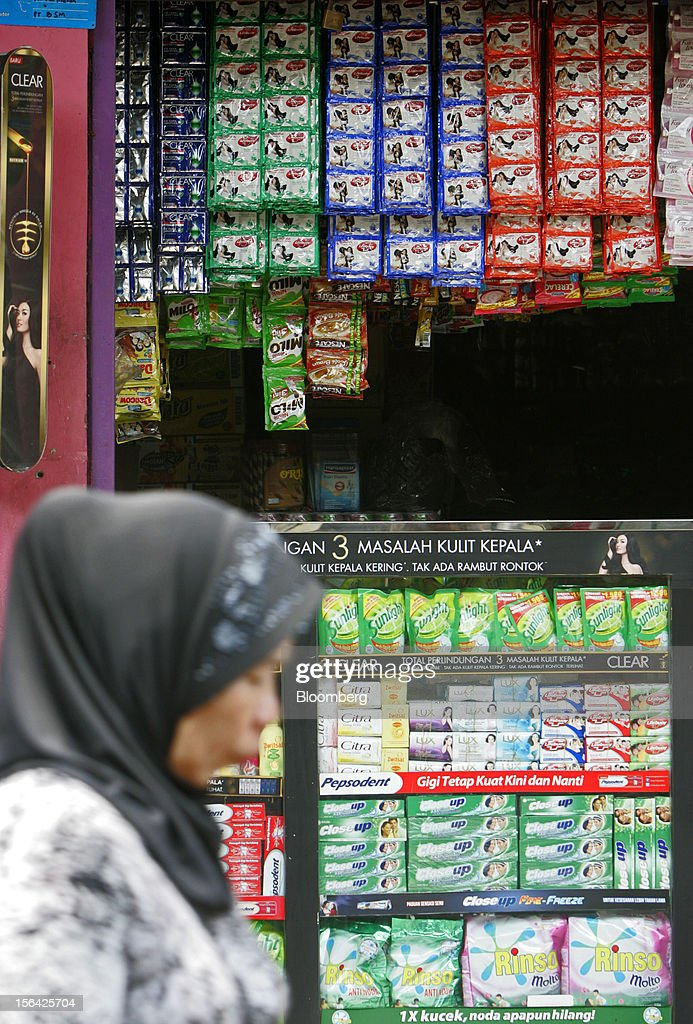 A woman walks past a store selling Unilever NV and Nestle SA products in Jakarta, Indonesia, on Wednesday, Nov. 14, 2012. Unilever has accelerated the rollout of shampoos and deodorants to emerging markets such as Indonesia and China to offset slowing growth in developed markets, where higher price tags have deterred consumers. Photographer: Dadang Tri/Bloomberg via Getty Images
