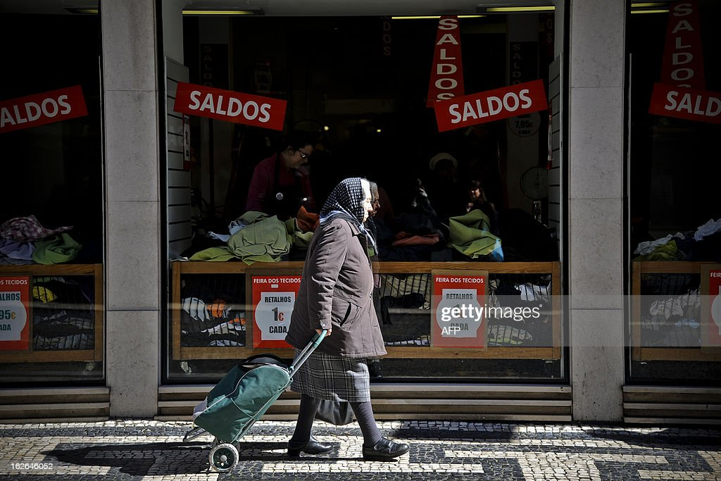 A woman walks past a store window displaying sales promotion advertisements in Lisbon on February 25, 2013. AFP PHOTO / PATRICIA DE MELO MOREIRA