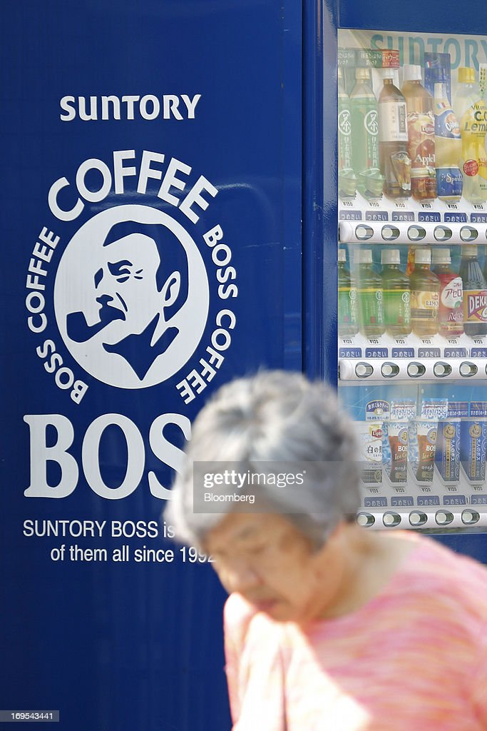 A woman walks past a Suntory Holdings Ltd. vending machine displaying the logo of Suntory Beverage & Food Ltd.'s Boss brand coffee in Tokyo, Japan, on Sunday, May 26, 2013. Nomura Holdings Inc., Morgan Stanley and JPMorgan Chase & Co. were selected as the lead banks to manage Suntory Beverage & Food Ltd.'s initial public offering, said two people with knowledge of the matter. Photographer: Kiyoshi Ota/Bloomberg via Getty Images