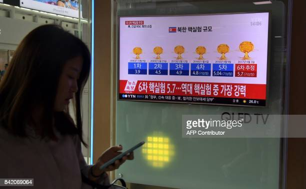 A woman walks past a television display at a train station in Seoul on September 3 2017 showing a news broadcast with a graphic about a history of...