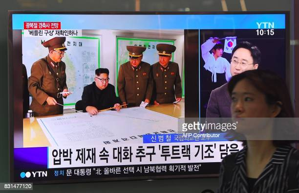 TOPSHOT A woman walks past a television news screen showing North Korean leader Kim JongUn receiving a briefing at a railway station in Seoul on...