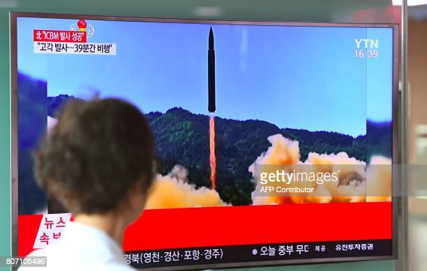 A woman walks past a television screen showing a picture of North Korea's launch of an intercontinental ballistic missile at a railway station in...