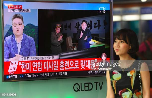 A woman walks past a television screen showing a video footage of North Korean leader Kim JongUn celebrating his country's latest test launch of an...