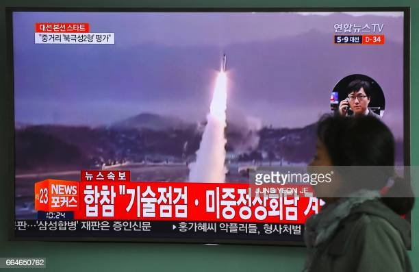 TOPSHOT A woman walks past a television screen showing file footage of a North Korean missile launch at a railway station in Seoul on April 5 2017...