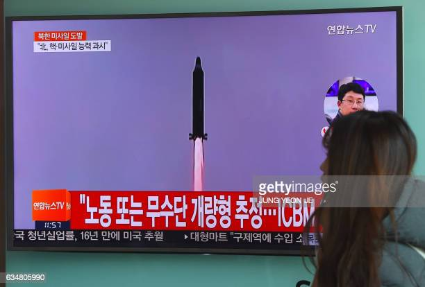 A woman walks past a television screen showing file footage of North Korea's missile launch at a railway station in Seoul on February 12 2017 North...