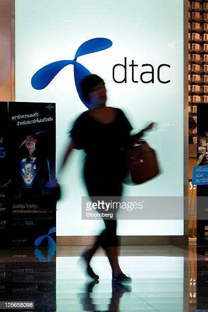 A woman walks past a Total Access Communication Pcl store at the company's headquarters in Bangkok Thailand on Monday Sept 19 2011 DTAC Thailand's...