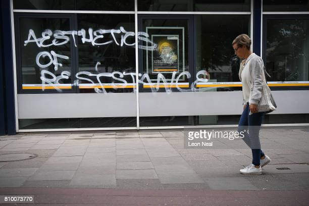 A woman walks past a vandalised bank following the 'Welcome to Hell' antiG20 protest march on July 7 2017 in Hamburg Germany Authorities are braced...