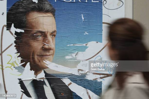 A woman walks past a vandalized election poster showing French President Nicolas Sarkozy the day before the second rounf of French Presidental...