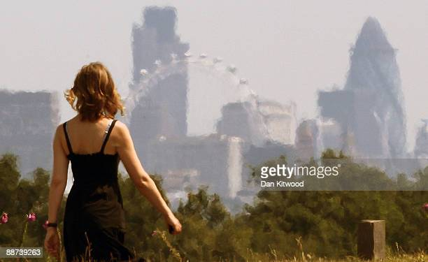 A woman walks past a view of the City of London in Richmond Park on June 29 2009 in London England The Met Office has announced a weather warning for...