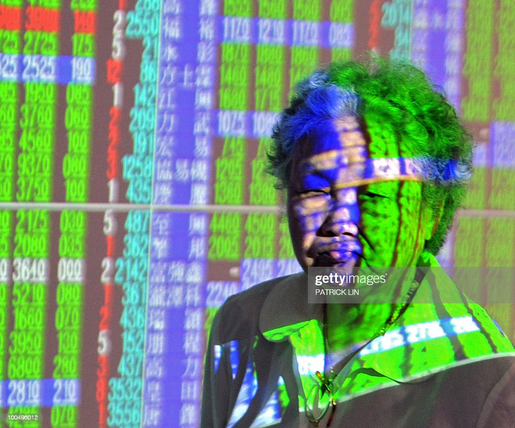 A woman walks past a wall of projected stock figures at a securities trading house in Taipei on May 25, 2010. Taiwan's weighted index tumbled 236.36 points, or 3.23 percent, at 7,086.37 on deepening worries about the eurozone debt crisis and the growing tensions on the Korean peninsula, dealers said.