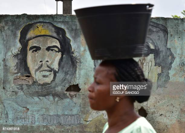 TOPSHOT A woman walks past a wall with a portrait of Argentineborn guerrilla leader Ernesto 'Che' Guevara in a quarter of Abidjan on November 14 2017...