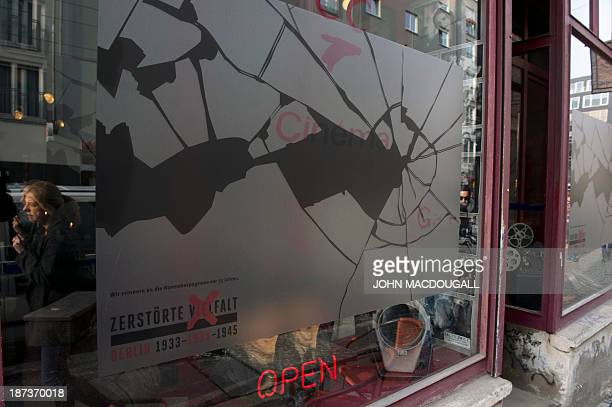 A woman walks past a window decorated with a sticker simulating broken glass at a cafe in Berlin November 8 ahead of the 75th anniversary of the...