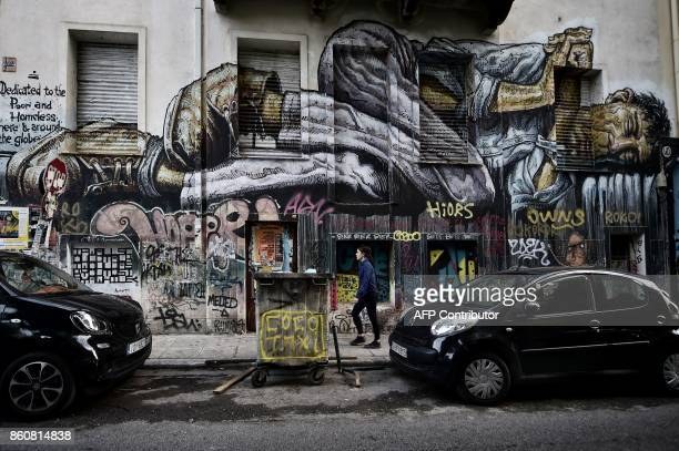 A woman walks past a work by a Baliborn graffiti artist WD in central Athens on October 11 2017 WD and Cacao Rocks are taking part in an ongoing...
