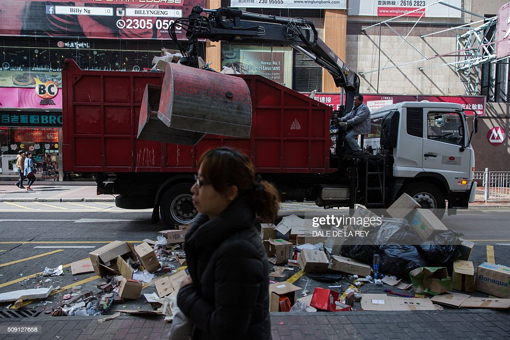 A woman walks past a worker clear debris from a street following overnight clashes between protesters and police in the Mongkok area of Hong Kong on February 9, 2016. Baton-wielding Hong Kong riot police fired warning shots and tear gas early on February 9 after a riot erupted in the busy district of Mongkok when officials tried to shift illegal hawkers, local radio reported. AFP PHOTO / DALE DE LA REY / AFP / DALE de la REY