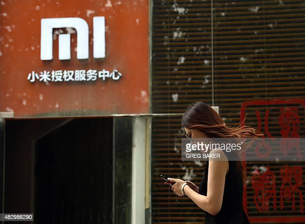 A woman walks past a Xiaomi logo outside a Xiaomi service center in Beijing on August 5 2015 Chinese company Xiaomi was the largest smartphone vendor...