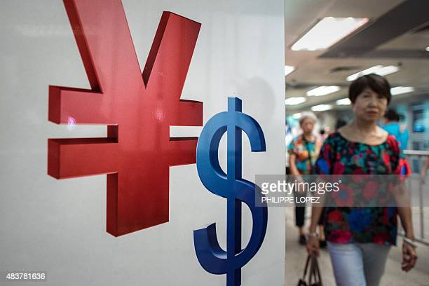 A woman walks past a yuan and a US dollar currency sign in Hong Kong on August 13 2015 China cut the reference rate for its currency for the third...