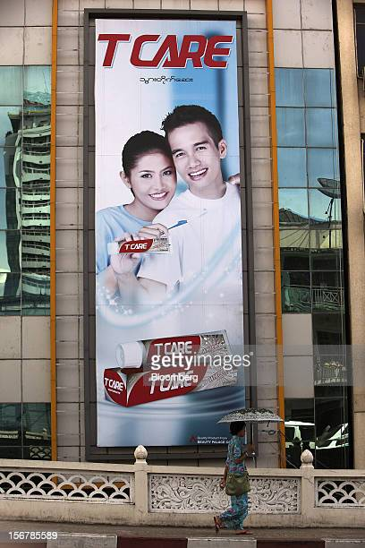A woman walks past an advertisement for T Care brand toothpaste in Yangon Myanmar on Tuesday Nov 20 2012 Myanmar's growth outlook has improved...