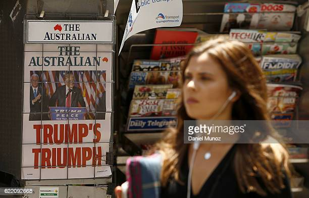 A woman walks past an advertisement for The Australian newspaper on November 10 2016 in Sydney Australia Americans voted yesterday to elect Donald...