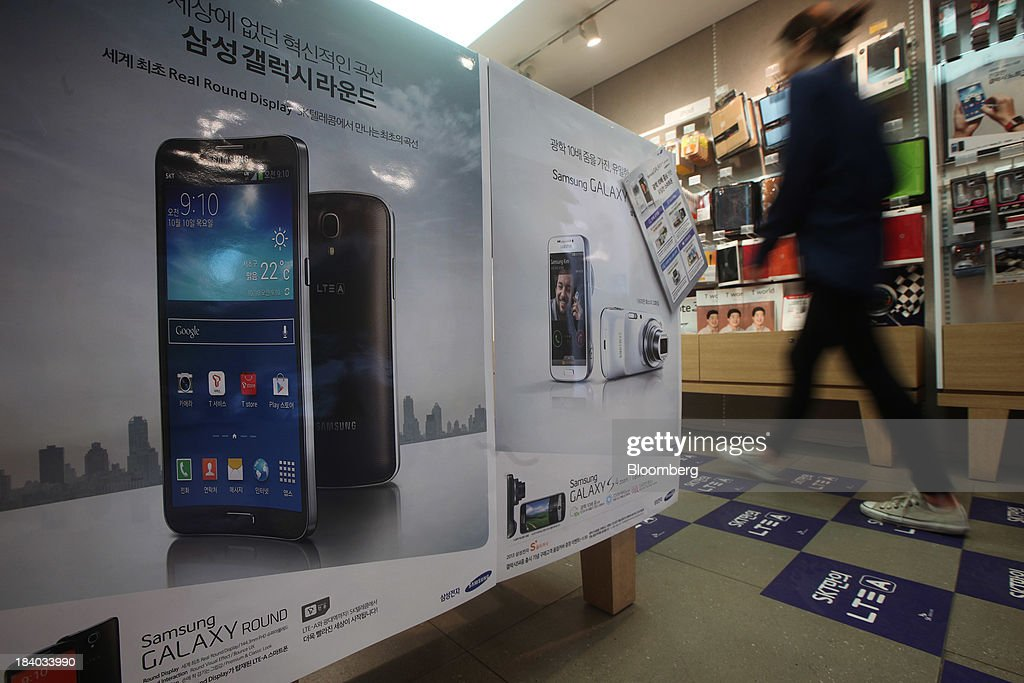 A woman walks past an advertisement for the Samsung Electronics Co. Galaxy Round smartphone at an SK Telecom boutique in the Jongro-gu area of Seoul, South Korea, on Friday, Oct. 11, 2013. Samsung will sell what it called the worlds first smartphone with a curved display as the largest handset maker moves toward devices with bendable screens in its competition with Apple Inc. Photographer: Woohae Cho/Bloomberg via Getty Images