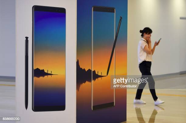 A woman walks past an advertisement for the Samsung Galaxy Note 8 at the company's showroom in Seoul on August 25 2017 The heir to the Samsung...